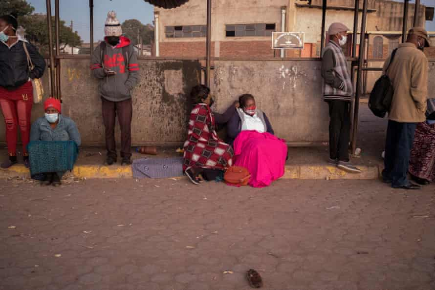 Mupombwi and her friend sit together in the queue