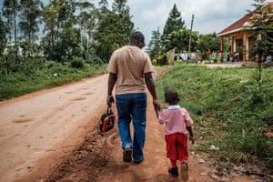 Daniel Kasolo walks with his son Keith back home in Nansana.