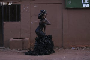A model poses outside in a black dress with ruffles at the bottom