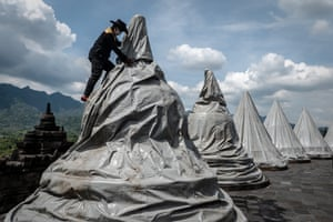 A worker covers a statue to prevent damage from volcanic ash at a temple in Magelang, Indonesia