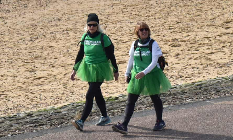 Two people in Macmillan outfits on Southend beach in February