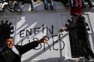 Tunisian protestors pictured in January 2011 before a wall on which the words 'Free at last' are daubed