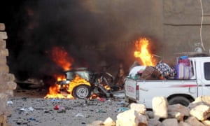 A car is engulfed by flames during clashes in the city of Ramadi.