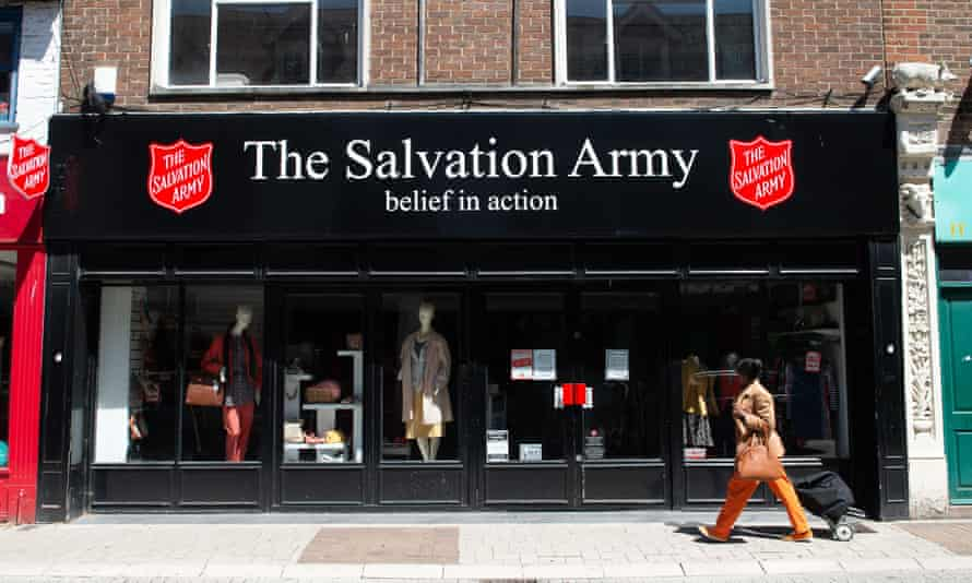 A woman walking past the black shopfront of a Salvation Army shop, which has a a white-lettered signboard with two red shields on either side
