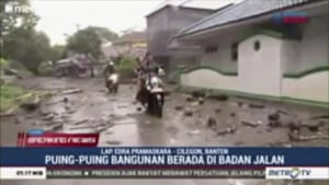 People ride motorbikes through water and debris-filled streets in Serang city.