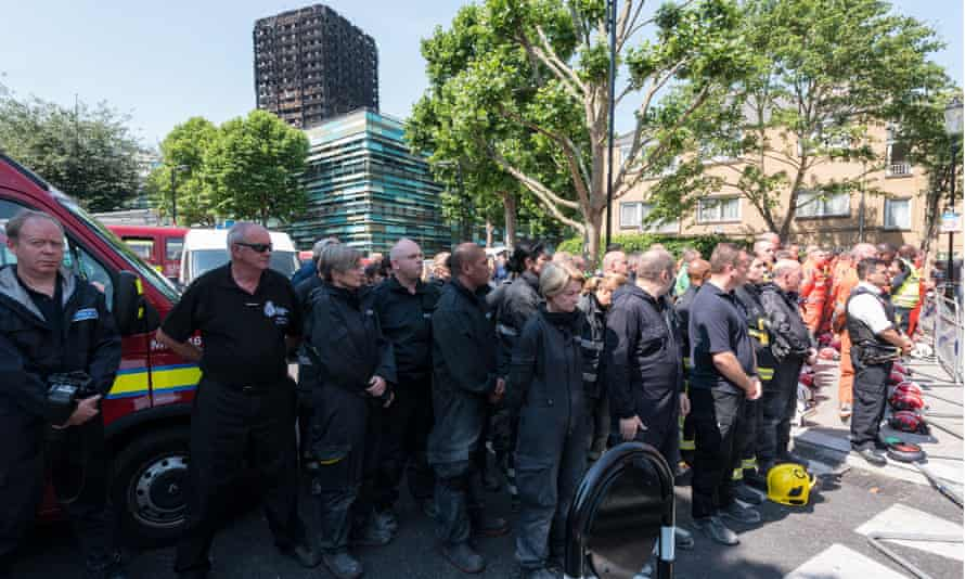Members of the emergency services observe a minute's silence near Grenfell Tower.