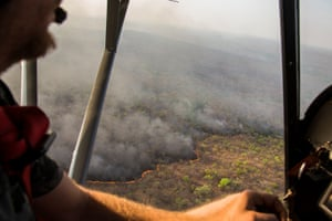 Cédric Ganière, one of the Chinko's pilots, flies over a bushfire on the savannah in his tiny, two-seater plane during a mission to spot blazes lit by cattle herders.