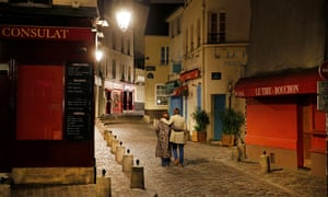 A couple walks on a deserted street at night on the Butte Montmartre in Paris.