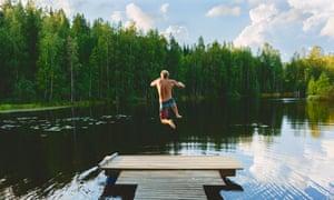 Finland, Keski-Suomi, Jyvaskyla, Lake Vuohijarvi. Young man jumping off pier into lake