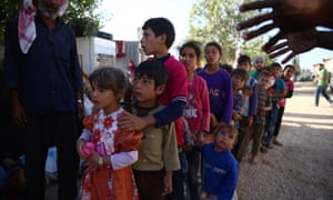 Syrian children queue to receive aid.