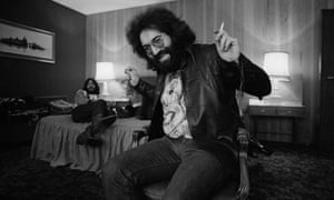 Jerry Garcia with a joint in his hand looking happy