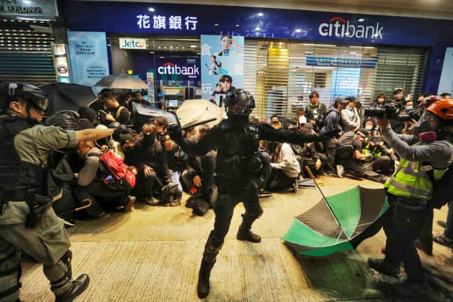 Riot police detain protesters.