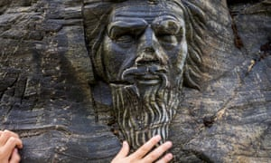 English Heritage has been criticised for installing a rock carving of Merlin in the cove beneath the castle