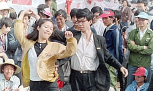 A young unidentified couple pass the time in Tiananmen Square with a lively dance.