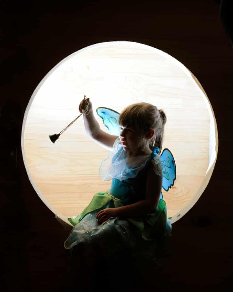A little girl holds the original Tinker Bell (a small bell that JM Barrie bought to be rung whenever his fairy character appeared in the original stage version of the story).