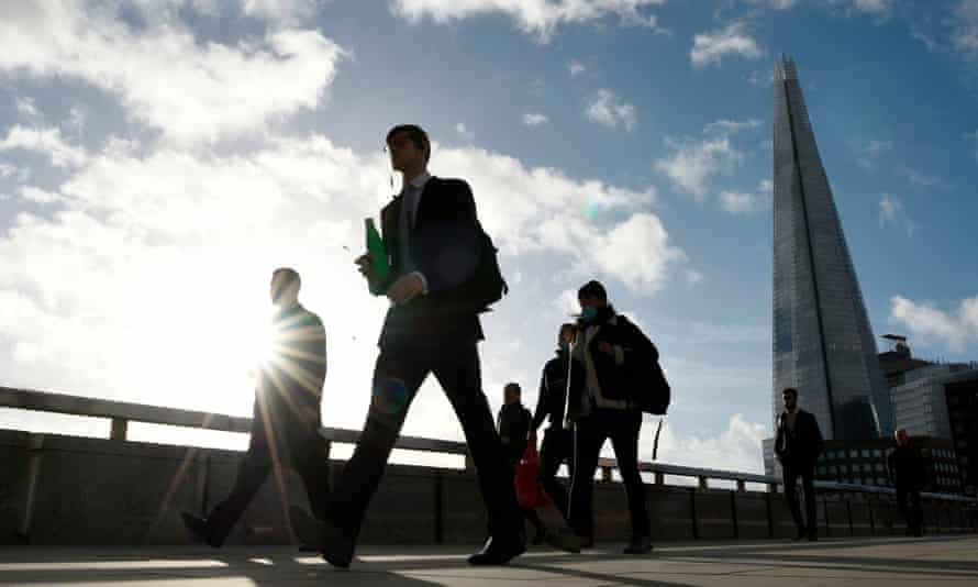 Commuters walk over London Bridge during the morning rush hour in London.