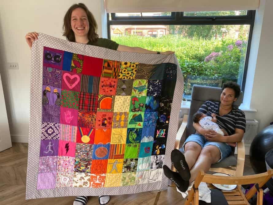 Lucy (left), Vee and their baby, Asher, with a quilt made for them by Ruth Evans
