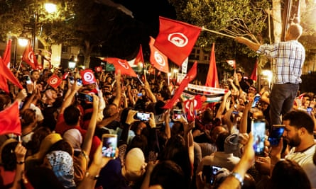 People celebrating in the streets of Tunis after exit polls suggested a win for Kais Saied in Tunisia's presidential election.