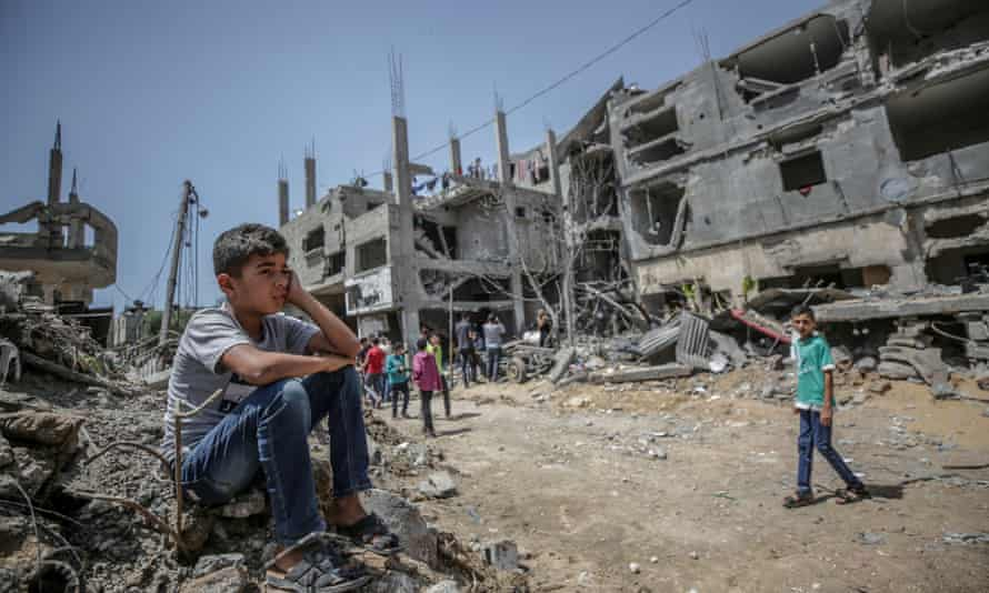 A Palestinian boy sits on the rubble of his house destroyed in an Israeli airstrike