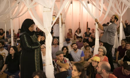 Waida Ibtisam Mahmeed ties up the strips of muslin that hang from the ceiling in preparation for an evening of prayer and song