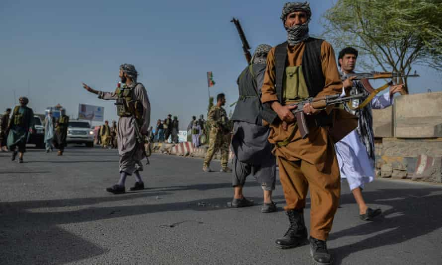 Afghan security personnel and militia fighting against the Taliban, stand guard in Enjil district of Herat province on Friday.