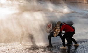Demonstrators use shields to protect themselves from water sprayed by riot police during clashes on the commemoration of the first anniversary of the social uprising in Chile, in Santiago, on 18 October.