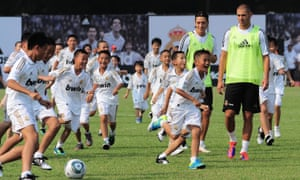 Mesut Özil and Karim Benzema playing with children from a Chinese football school during Real Madrid's pre-season tour in 2011