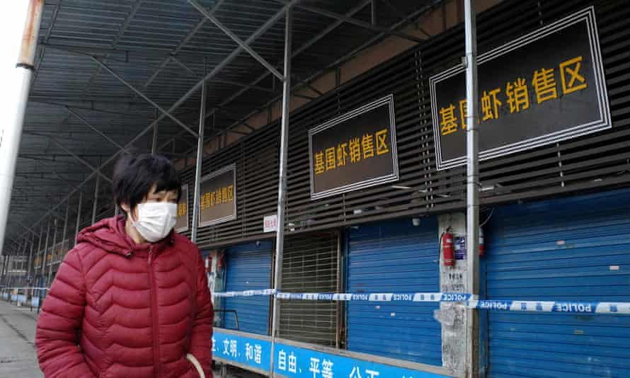 A woman walks by a closed seafood market in Wuhan on 12 January.