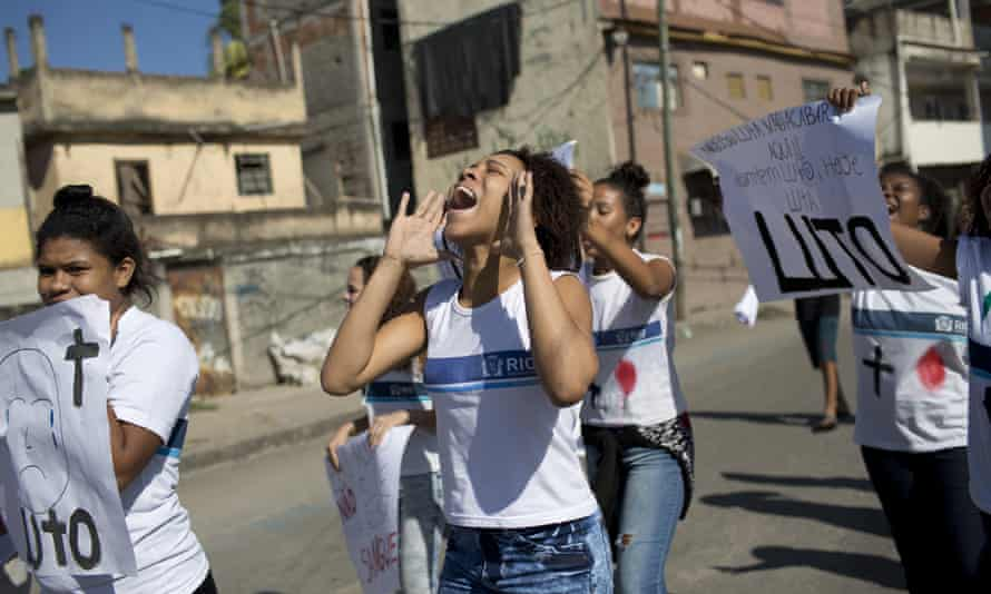 Students and friends of Marcus da Silva hold signs that read 'Mourning' during a protest in Rio de Janeiro on 21 June.