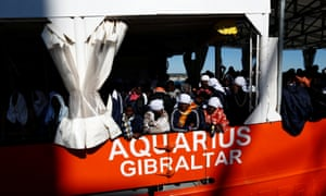 Migrants wait to disembark from the Aquarius on 18 December