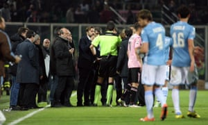 The referee talks to officials from Palermo and Lazio after flares were thrown on to the pitch by Palermo fans.