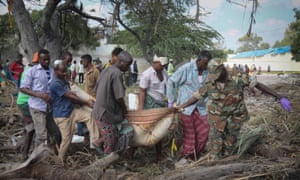 People carry the body of a victim through debris after a truck bomb went off outside Mogadishu's port.