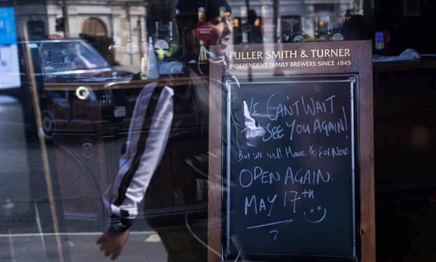 A member of the public walks past a closed pub in London, England.