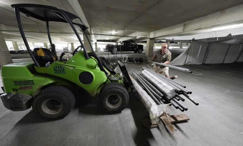 Jay McCullough arranges tent poles as a team of event specialists start to convert a parking garage at the University of Mississippi Medical Center into a field hospital on Wednesday in Jackson, Mississippi.