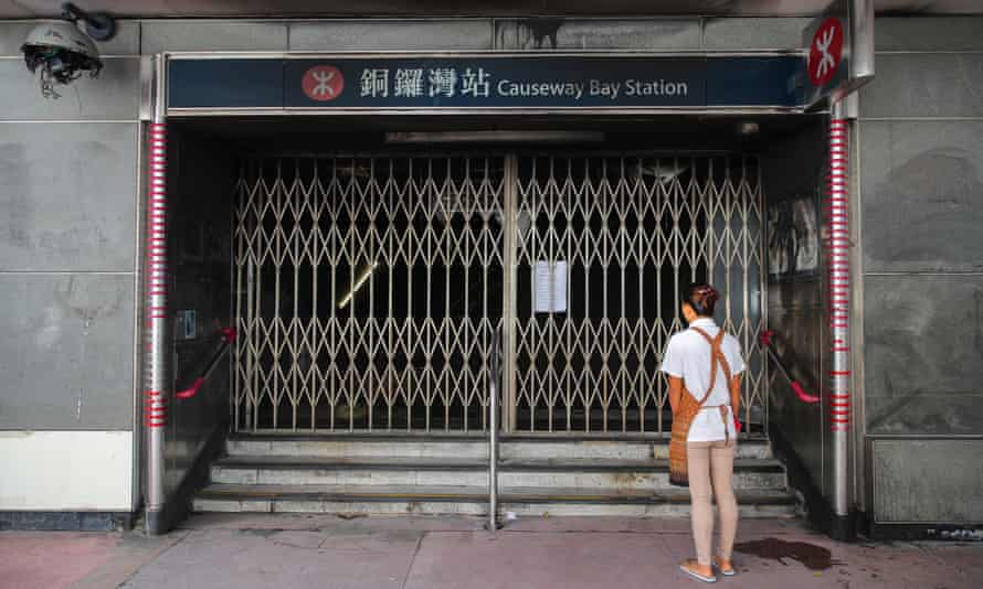A woman stands in front of a closed entrance gate to the Causeway Bay MRT train station
