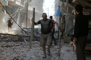 A man covered with dust carries debris down a rubble-filled street