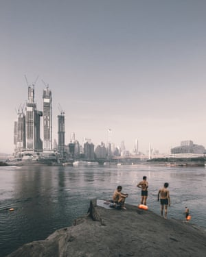 Swimmers on the riverside opposite the construction of Raffles City Chongqing, China by Safdie Architects