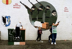 Catholic children play with toy guns under an IRA mural in south Belfast.