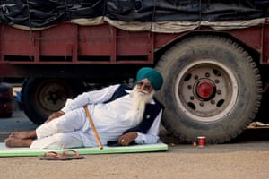 A farmer rests besides a tractor during the protest