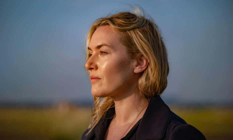 Kate Winslet staring out to sea in a blue coat