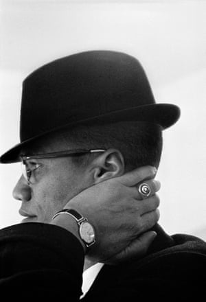 Profile of Malcolm X in a trilby, his left hand resting on his neck