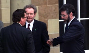 Northern Ireland's First Minister David Trimble chats with opponent Gerry Adams, along with Sinn Fein's Chief negotiator Martin McGuinness on 30 March 1999.