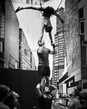 A woman does a handstand split on top of a man who is standing on another man's shoulders