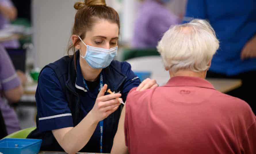 An NHS worker administers a coronavirus vaccine shot at Robertson House in Stevenage, UK.