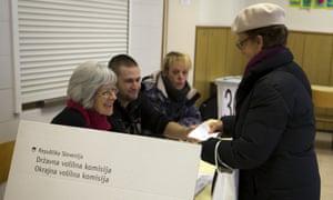 A voter registers at a polling station in Ljubljana for the same-sex marriage referendum.