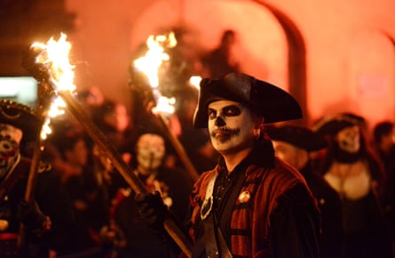 A man in traditional dress holds a flaming torch at Lewes' bonfire celebrations in 2015.