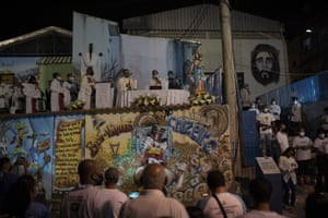 People pray and mourn during a mass for the victims of a deadly police raid outside the Nossa Senhora Auxiliadora church in the Jacarezinho favela in Rio de Janiero, Brazil