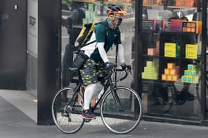A man wears a mask as he cycles around Sydney.