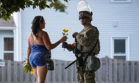 A woman hands flowers to a member of the Wisconsin national guard standing by as people gather for a vigil on Friday, following the police shooting of Jacob Blake.
