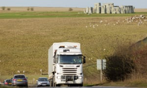 Trucks and traffic pass near by Stonehenge.
